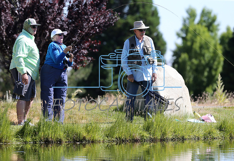 Jon Blakely, left, and George Liddell watch as breast cancer survivor Peggy Limi, of Bakersfield, reels in a fish during a Casting for Recovery retreat in Gardnerville, Nev., on Friday, June 30, 2017. The nationwide program, hosted locally with Carson Tahoe Cancer Center, pairs cancer survivors with fly-fishing guides.   <br />