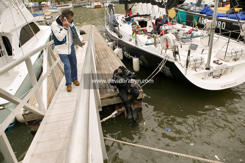 9 May 2006 - New York City, NY - Diver Edward Moreno (C) prepares to dive to check the hulls of yatchs moored at the North Cove Marina in New York City, USA, between two legs of the 32,700 nautical miles-long Volvo Ocean Race. A local commmercial diver, he has been hired by the teams to look after the yatchs' hulls that do not have a protective coating in order to increase speed. Photo Credit: David Brabyn