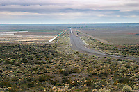 One of the long straight dirt roads across the big property and the natural vegetation of the plain desert in the foreground Bodega Del Fin Del Mundo - The End of the World - Neuquen, Patagonia, Argentina, South America