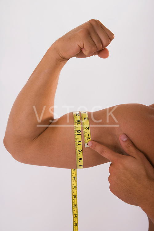 Man holding tape measure around flexed muscle, close-up