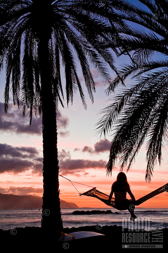 Woman on a hammock watching the sunset at Puaena Point, Haleiwa, on the North Shore of Oahu, Hawaii
