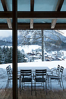Metal chairs and a table partially covered in snow furnish the covered terrace which looks down on the picturesque village beyond