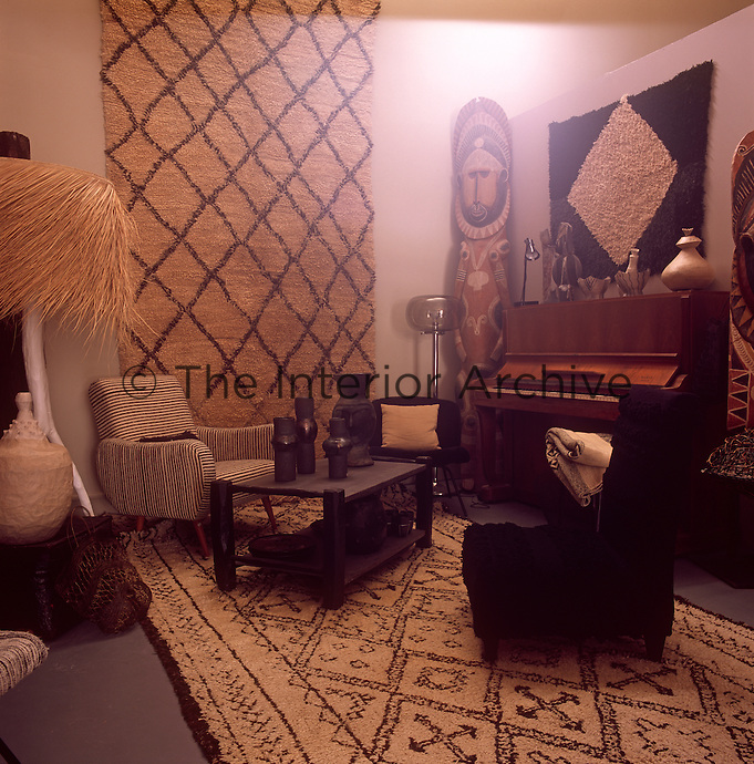 An ethnic styled living room with patterned textured wall hangings and rugs in neutrals and brown. An upright piano stands against one wall and two armchairs are placed either side of a wood coffee table.
