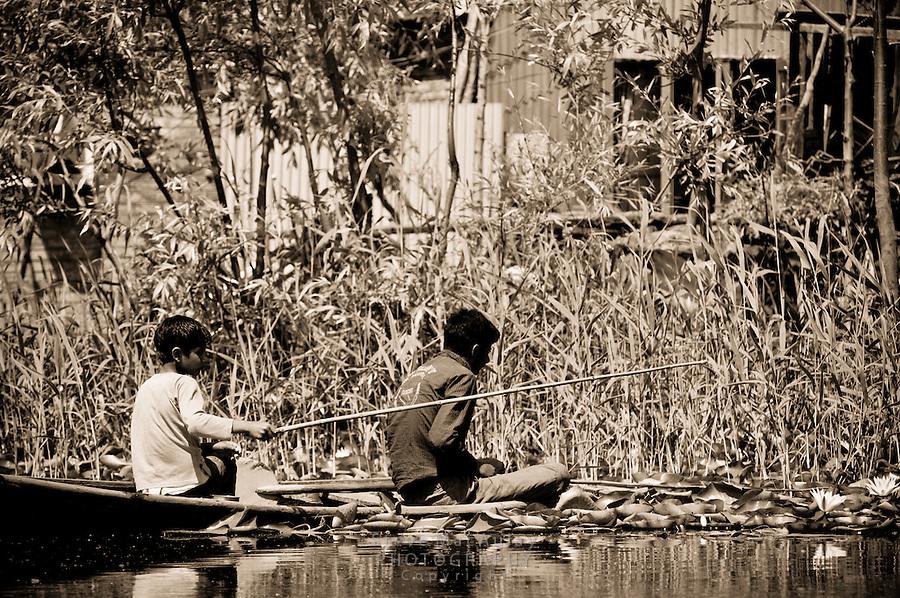 Young boys fishing from shikara boat, Dal Lake, Srinagar, Kashmir, India.