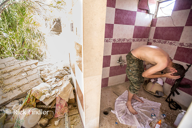 August 2017. Raqqa, Syria.<br /> Foreign volunteer fighter 'Macer Gifford', washes in an abandoned house on the front lines of western Raqqa. <br /> The MFS (Syriac Military Council) are a group of Assyrian Christians who fight alongside the Syrian Democratic Forces in the fight to topple ISIS.<br /> Photographer: Rick Findler