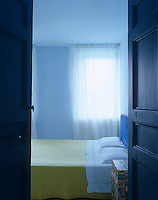 A pair of blue double doors open onto a simply furnished bedroom