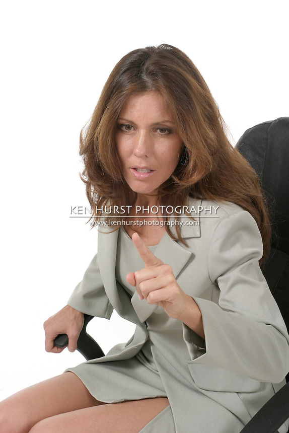 Beautiful brunette executive business woman in a business suit sitting in office chair, pointing and gesturing as if to give a warning.
