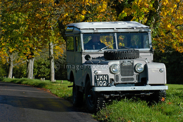 Grey 1950's Land Rover Series One 86 inch Station Wagon on country road in southern England. This Land Rover is in extremly original condition still with its original paint. Lovely autumn weather with beautiful coloured treas and blue sky. Dunsfold, UK, 2004. --- No releases available. Automotive trademarks are the property of the trademark holder, authorization may be needed for some uses.