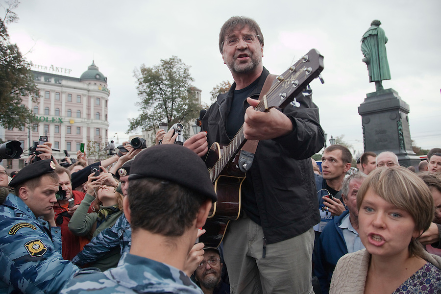 Moscow, Russia, 22/08/2010. .Legendary Russian rock star Yuri Shevchuk, flanked by ecological activist Yevgenia Chirikova, performs on a step ladder in Pushkin Square, where some 3,000 people gathered for a concert and protest against the destruction of part of Khimki Forest in northern Moscow as part of a motorway project. The concert was banned and police seized the performers' musical equipment, but unusually the anti-government protest was allowed to take place, although a number of opposition organisers were arrested on their way to the demonstration.