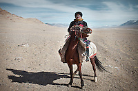"Haji Roshan, current ""Khan"" of the Afghan Pamir and son of the late Abdul Rashid Khan. On his way home on his horse. ..Ech Keli, Er Ali Boi's camp, one of the richest Kyrgyz in the Little Pavmir..Trekking with yak caravan through the Little Pamir where the Afghan Kyrgyz community live all year, on the borders of China, Tajikistan and Pakistan."