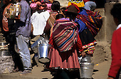 Paucartambo, Peru. Woman wearing traditional dress and carrying galvanised buckets from the back.