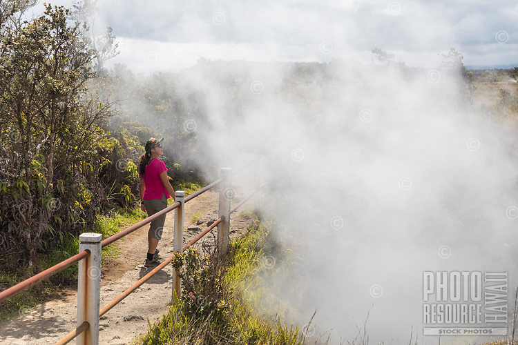 A woman walks past steam vents at Hawai'i Volcanoes National Park, Big Island.