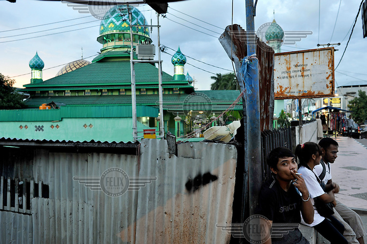 Youths hanging around near a mosque in one of the Muslim areas in predominately Christian Ambon City. The 1999-2002 religious war between Maluku's Christian and Muslim populations, mainly centred on Ambon Island, led to over 5000 deaths and to around 500,000 people become displaced. Destroyed homes and offices, churches and mosques are slowly being either torn-down or renovated.  Urban centres, such as Ambon City, continue to be split along largely sectarian lines, and tensions are never far below the surface. Riots between Christian and Muslim youths erupted in September 2011 and, most recently, June 2012, though luckily simmered down just as quickly, partly due to community leaders learning how to defuse tensions from the earlier, more devastating, conflagration. /Felix Features