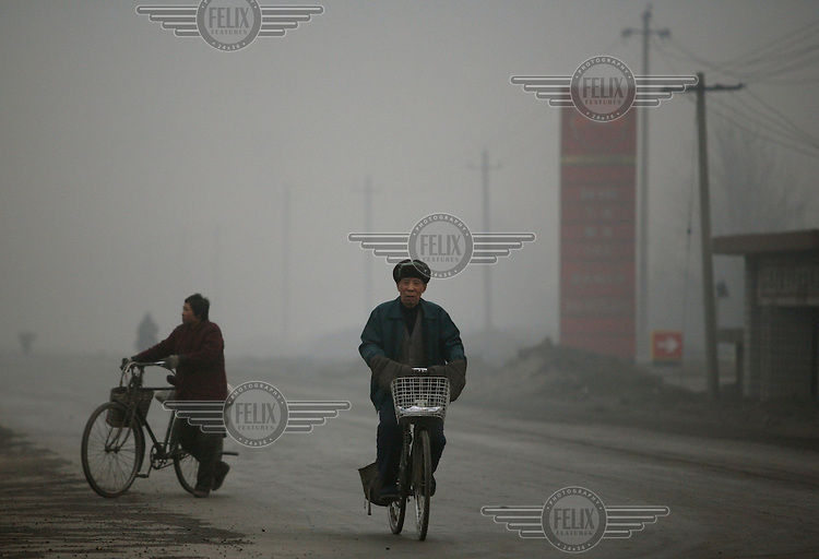 A resident rides a bicycle down a road engulfed in air pollution. With extremely high levels of air pollution, Linfen is reputed to be one of China's most polluted cities.