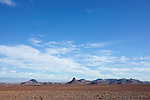 Desert landscape with volcanic mountains and cloudy blue sky, Sahara desert, Morocco.