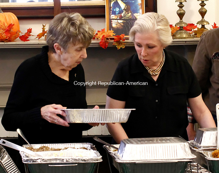 """Woodbury, CT- 27 November 2014-112714CM04-Volunteers, Diana Neal, left, of Woodbury and Pat Heeg of Bethlehem prepare to serve dinner during the 15th annual free Thanksgiving dinner put on by First Congregational Church in Woodbury on Thursday.  Event organizer, Skip Jaret said the free dinner was open to everyone and featured food donated by the members of the church along with various people and businesses from the community.  """"This has to be one of the most fulfilling events of my life.  It's truly the real meaning of Thanksgiving, said Jaret.   Christopher Massa Republican-American"""