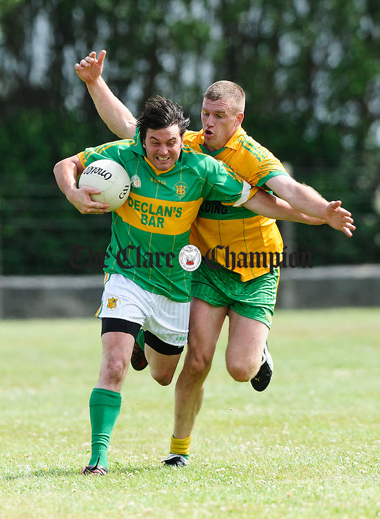 Mark O Connell of Kilmihil is tackled by Ger Quinlan of O Curry's  during their game at Doonbeg. Photograph by John Kelly.