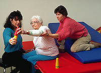 Two physical therapists work with an elderly woman in a rehabilitation hopital.