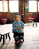 CHINA, Longsheng, portrait of girl in traditional clothing sitting at table in Longsheng