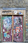 Spitalfields, London. artistic graffiti on a rough side door to a building with posters and tags; padlock, hasp.