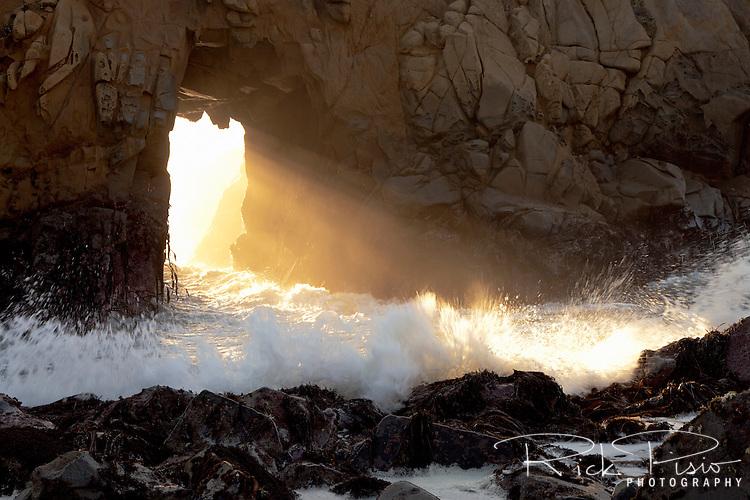Sunlight and surf stream through Keyhole Arch at Pfeiffer Beach along California's Big Sur Coastline.