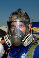 Sept. 19, 2010; Concord, NC, USA; An NHRA fan wears a gas mask to protect from the nitro methane fumes as a funny car warms up its engine in the pits during the O'Reilly Auto Parts NHRA Nationals at zMax Dragway. Mandatory Credit: Mark J. Rebilas-