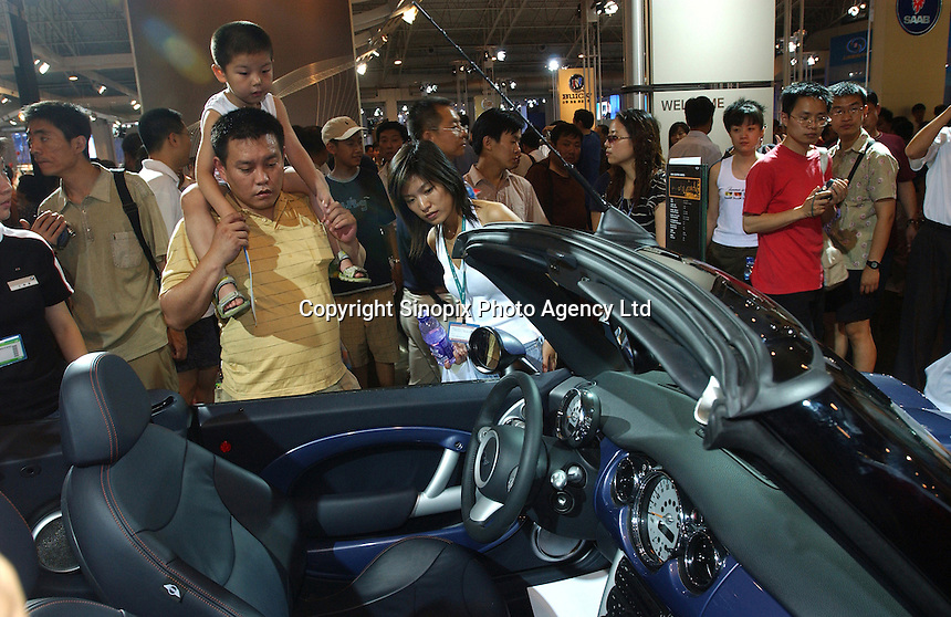 A family looks at a Mini Cooper display at the Auto China 2004 exhibition in Beijing, China..