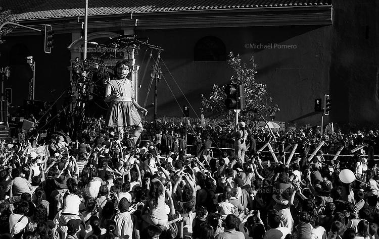 """31.01.2010 Santiago de chile (Chile)<br /> <br /> FOR THE BICENTENARY OF CHILE,SANTIAGO MIL AND THE CITY OF SANTIAGO INVITE  THE WONDERFUL """" PEQUENA GIGANTE """" FROM THE FRENCH STREET ART COMPANY """"ROYAL DE LUXE"""".<br /> <br /> THE """"PEQUENA GIGANTE"""" DURING THREE DAYS WAS FOLLOWED ON ALL MEDIAS AND ABOVE ALL BY MILLIONS OF PEOPLE IN THE STREETS OF THE CAPITAL SANTIAGO.<br /> <br /> THE SHOW IS VERY UNIQUE, POETIC,POPULAR AND GENERATE ALSO A LOT OF ENTHUSIASM AND EXCITATION TO CHILDRENS AND FAMILIES.<br /> <br /> THIS HUGE PUMPET IS DRIVEN IN THE STEETS BY A LOT OF MENS WHO ARE PLAYING THEIR ROLE LIKE LILIPUTIANS.<br /> <br /> <br /> <br /> <br /> POUR LE BICENTENAIRE DU CHILI,SANTIAGO MIL ET LA VILLE DE SANTIAGO INVITENT LA MERVEILLEUSE """"PEQUENA GIGANTE"""" DE LA COMPAGNIE D'ART DE RUE FRANCAISE """"ROYAL DE LUXE"""".<br /> <br /> DURANT TROIS JOURS """"LA PEQUENA GIGANTE"""" FUT SUIVIE SUR TOUS LES MEDIAS ET SURTOUT PAR DES MILLIONS DE PERSONNES DANS LES RUES DE LA CAPITALE SANTIAGO.<br /> <br /> LE SPECTACLE EST UNIQUE,POETIQUE,POPULAIRE ET GENERE AUSSI BEAUCOUP D'ENTHOUSIASME ET D'EXCITATION AUPRES DES ENFANTS ET DES FAMILLES.<br /> <br /> <br /> LA GIGANTESQUE MARIONNETTE EST ARTICULEE ET COINDUITE DANS LES RUES PAR DE NOMBREUX HOMMES JOUANT LE ROLE DES LILIPUTIENS."""