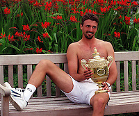 WIMBLEDON CHAMPIONSHIPS 2001 09/07/01 MENS FINAL GORAN IVANISEVIC (CROATIA) V PAT RAFTER GORAN IVANISEVIC RELAXES WITH TROPHY AFTER  FIVE SET VICTORY PHOTO ROGER PARKER