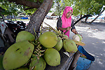 Rusmiati cuts coconuts that she sells at her stand on the tourist beach at Lhok Me, in Indonesia's Aceh province. The woman was left homeless by the 2004 tsunami, but YEU, a member of the ACT Alliance, worked with the village to build new houses in a safer area, as well as help revitalize their income generating activities. The tsunami killed 221,000 people in Aceh province and left more than 500,000 displaced.