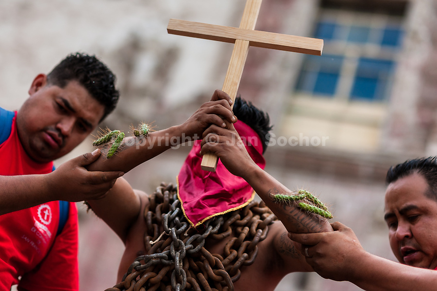A hooded Catholic penitent, wearing chains and cactus spines stuck to his body, raises a wooden cross during the Holy week procession in Atlixco, Mexico, 30 March 2018. Every year on Good Friday, dozens of anonymous men of all ages voluntarily undergo pain and suffering during the religious procession of the 'Engrillados' (the Shackled ones) in Puebla state, central Mexico. Wearing heavy chains on their shoulders covered with prickling cacti while being burned by the hot midday sun, they recall Jesus Christ's death by crucifixion and demonstrate their religiosity and faith.