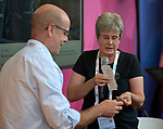 Sara Speicher of the World Council of Churches Ecumenical Advocacy Alliance hands material about the WCC's Thursdays in Black campaign to Tim Martineau, acting executive director of UNAIDS, during a July 26 seminar in the Global Village of the 2018 International AIDS Conference in Amsterdam, Netherlands. The presentation was co-sponsored by the United Nations and the World Council of Churches Ecumenical Advocacy Alliance.