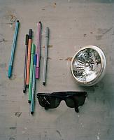 A still life of sunglasses, coloured pens and a lightbulb on a desk