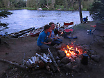 Two girls at a campfire along the St. Croix River, Maine, USA