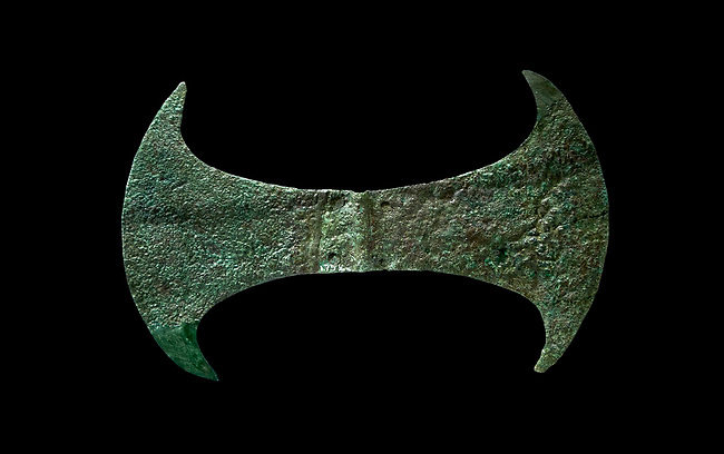 Minoan  cult bronze double axe 'labrys',  1600-1400 BC, Heraklion Archaeological  Museum, black background.<br /> <br /> In Minoan Crete, the double axe was an important sacred symbol of the supposed Minoan religion. In Crete it never accompanies male gods, only female goddesses. It seems that it was the symbol of the arche of the creation (Mater-arche).