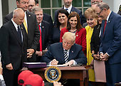 United States President Donald J. Trump signs S. 2372 – VA Mission Act of 2018 at the White House in Washington, DC, June 6, 2018. Credit: Chris Kleponis / CNP