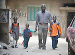Abdel Karim, a refugee from the Darfur region of Sudan, walks his children to school in the morning through the streets of Cairo, Egypt. Karim and his wife have both taken adult education classes provided by St. Andrew's Refugee Services, which is supported by Church World Service. His children, from left, are Dana, 7; Ahmed, 4; and Ziad, 9.