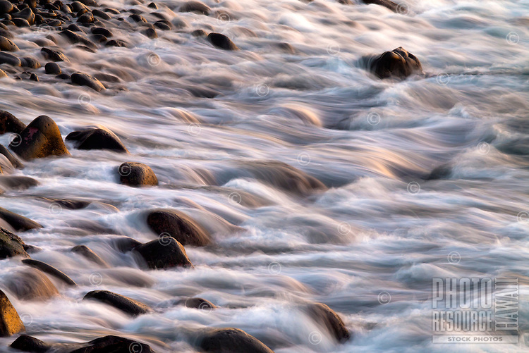 Water surges back into the ocean over the boulders of the rocky shoreline at Keahole Point, Big Island.