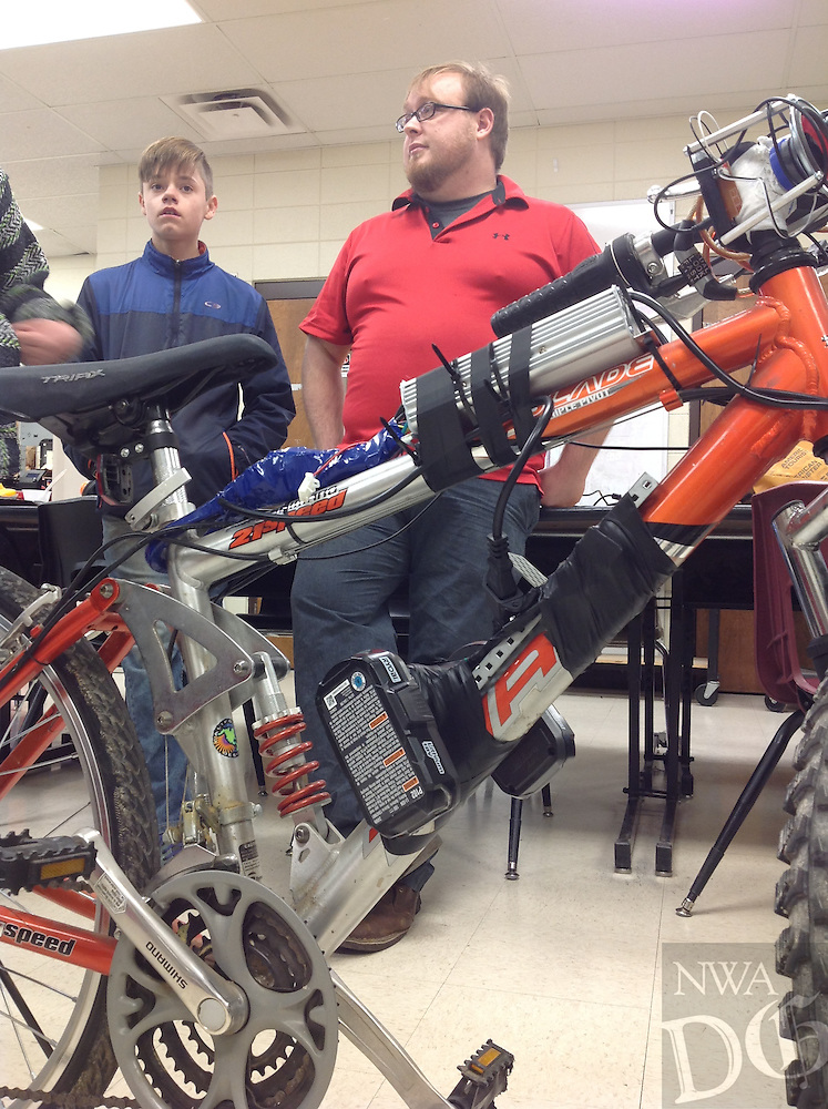 NWA Democrat-Gazette/Dave Perozek<br /> Blake Matthews, a science and technology teacher at Washington Junior High School, stands with an electric bicycle assembled last month by some of his students.