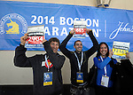 (Boston Ma 042014) Friends Ted McCarthy, 29, of Seattle Wa. left,  Mark Hutchkiss 27, of Littleton Co. center, and Brandy Adler, 28, of Boston, wave their bib numbers  to friends and family looking on, at the Hynes Center in Boston, Sunday, April 20, 2014, the day before the Boston Marathon. (Jim Michaud Photo) For Sunday