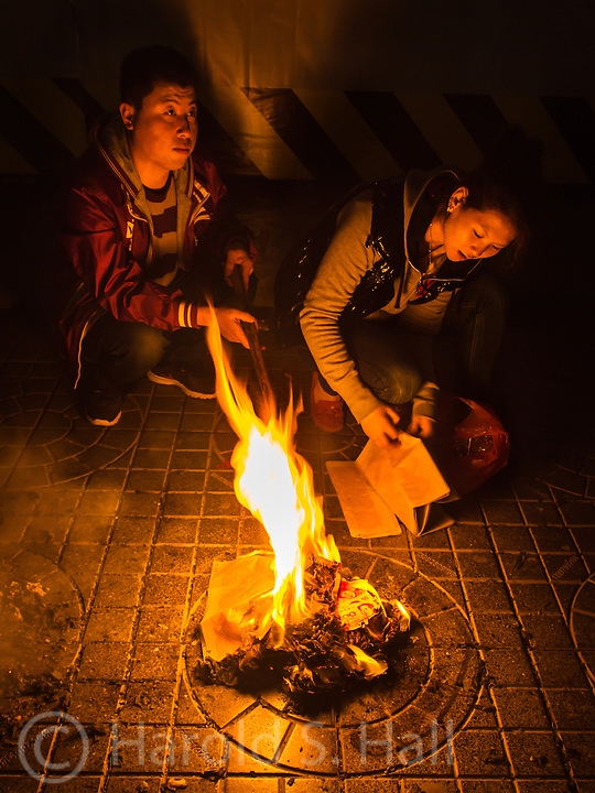 This two children are burning special money for their deceased parents so they will have some cash in heaven.....  If you look into the fire you will see red colored money with a photo of Chairman Mao.  The smoke takes the money into the heavens.  While in China, we saw several such fires and would see some of this discarded money laying in the streets.  This practice was banned by the Communists but the annual celebration called Qingming has recently been reinstated.