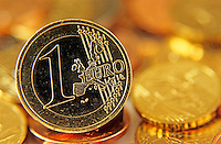 One Euro coin standing-up amongst other Euro coins