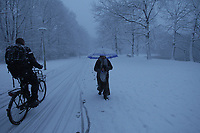 AMSTERDAM,NETHERLANDS - DECEMBER 11: A man ride bicycle and woman walking at the Rembrandt Park during heavy snowfall on December 11, 2017 in Amsterdam,Netherlands. The Dutch weather bureau issued a code red weather warning for many places in the Netherlands.