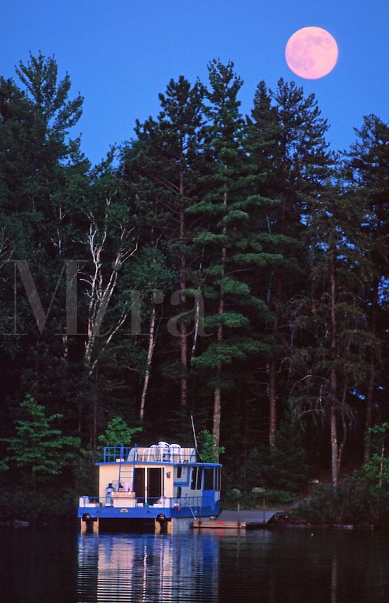 Houseboat docked ona lake with full moon.