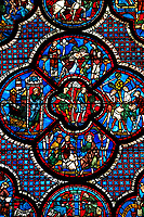 Medieval stained glass Window of the Gothic Cathedral of Chartres, France - dedicated to the lGood Samaritan . Central panel shows A bandit prepares to attack the pilgrim , below  - Christ telling the parable to a couple of Pharisees, left -The pilgrim leaving Jerusalem, right -  The pilgrim is beaten, robbed and stripped , above - A Priest and a Levite see the injured man but walk on past. A UNESCO World Heritage Site.