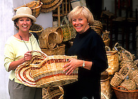 Two tourist women finding bargains in straw market in romantic Tuscany Greve in Chiant