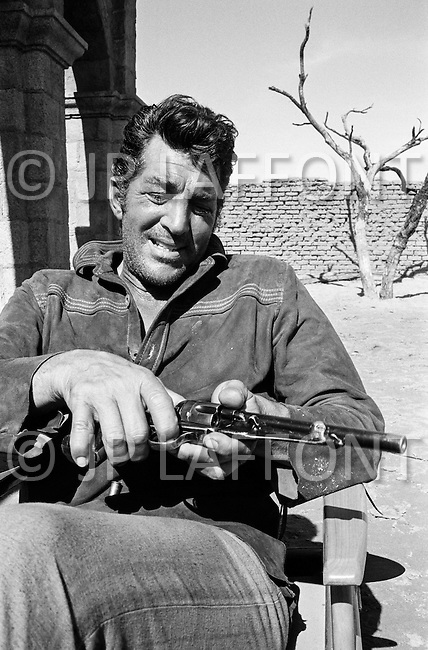 """1967, Del Rio, Texas, USA --- Actor Dean Martin handles his revolver on the set of """"Bandolero!"""" in Del Rio, Texas. In the movie, Martin plays the character Dee Bishop. The film was directed by Andrew V. McLaglen. --- Image by © JP Laffont"""