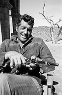 "1967, Del Rio, Texas, USA --- Actor Dean Martin handles his revolver on the set of ""Bandolero!"" in Del Rio, Texas. In the movie, Martin plays the character Dee Bishop. The film was directed by Andrew V. McLaglen. --- Image by © JP Laffont"