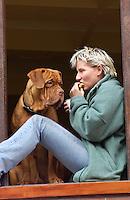 Nederland, Amsterdam, 2-2-2002..Jonge vrouw zit in het raam met haar hond. Ze eet wat, hond kijkt er wanhopig naar...Foto (c) Michiel Wijnbergh/Hollandse Hoogte.