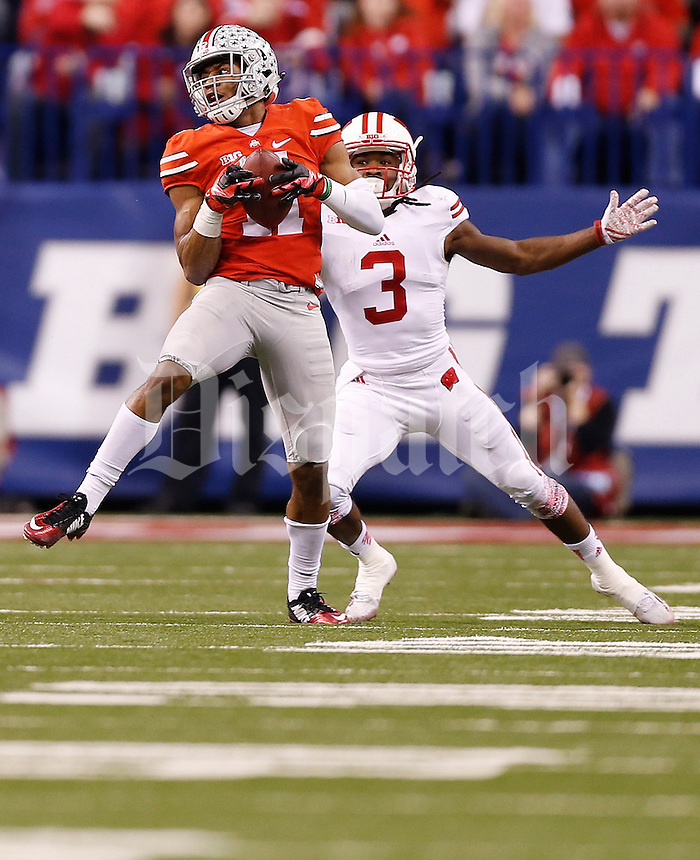 Ohio State Buckeyes defensive back Vonn Bell (11) catches an interception meant for Wisconsin Badgers wide receiver Kenzel Doe (3) in the first quarter of the Big Ten Championship game between the Ohio State Buckeyes and the Wisconsin Badgers at Lucas Oil Stadium in Indianapolis, Saturday night, December 6, 2014. (The Columbus Dispatch / Eamon Queeney)